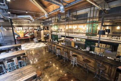 empty pub with long wooden tables, stools at the bar and industrial pipes on the ceiling