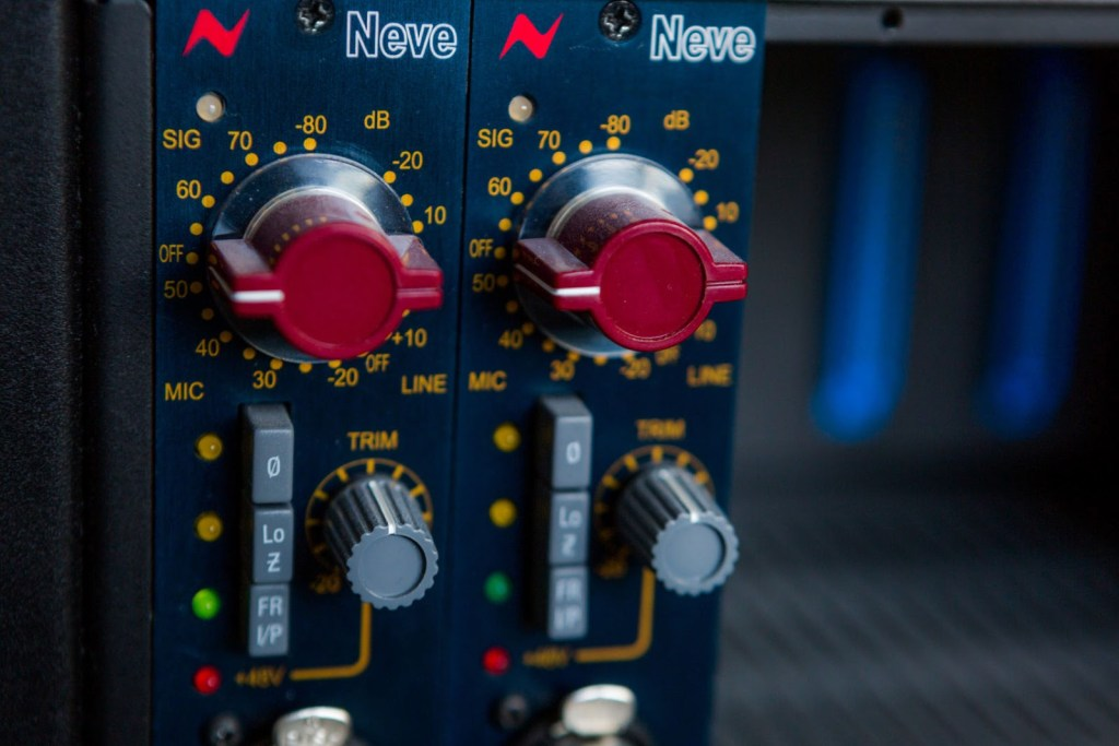 A close up of red circular dials on a recording system