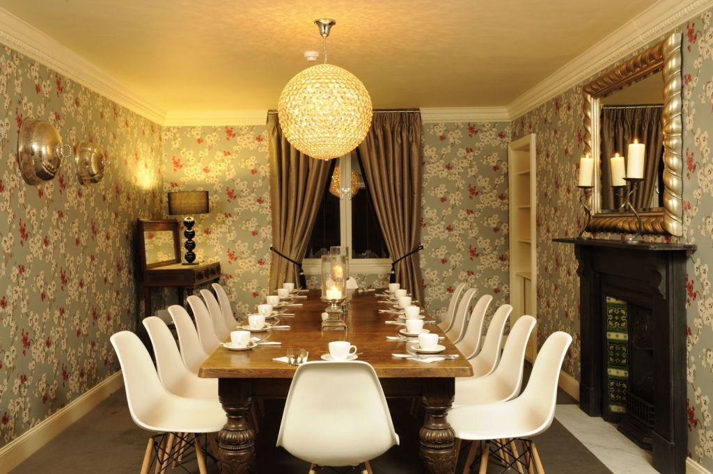 A meeting room in Edinburgh with flower wallpaper and a large circular light.