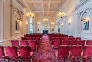 A grand livery hall with high white ceilings and rows of red chairs one of the best hotels with conference facilities