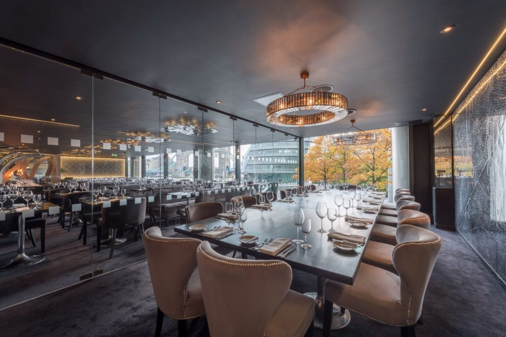 A private dining room which back wall is a floor to ceiling window that offers stunning views out over the city