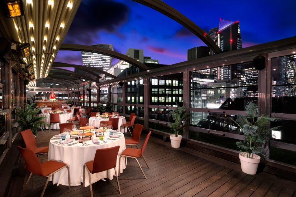 A rooftop bar in London with tables set for dinner and an open roof. The space has an amazing view of the city skyline