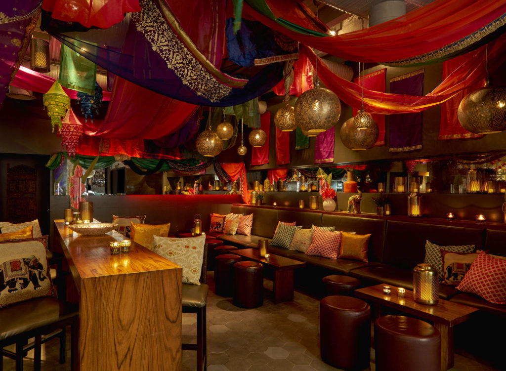 The Cinnamon Bazaar at Anise Bar with hanging lights over cushioned seats at tables with candles