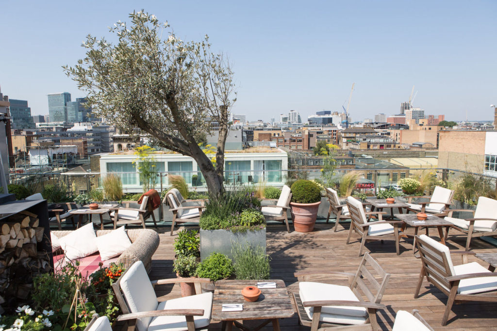 Rooftop deck with tables and chairs surrounding by shrubbery overlooking London