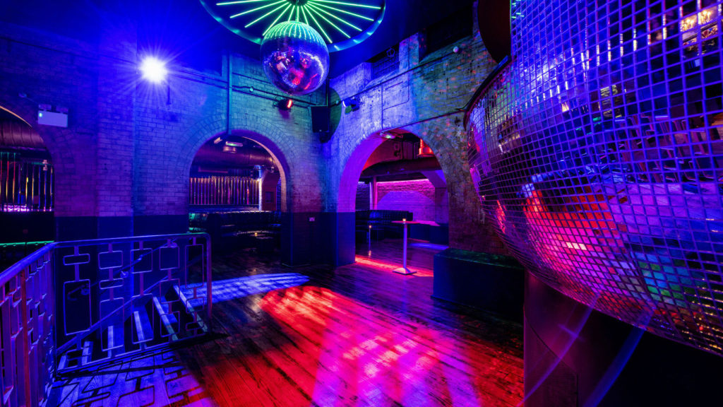 Large disco ball overlooking a dance floor that is flooded with lights of different colours