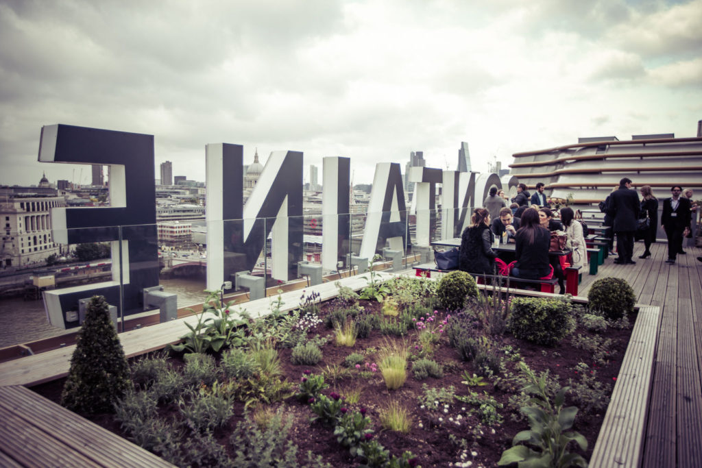 Deck looking out over London with the large Sea Containers lettering, bank of shrubs and guests