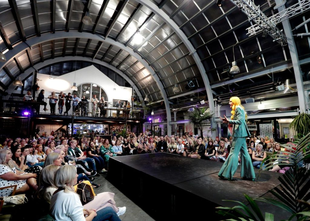 A speaker on a raised stage addresses a large crowd in a large event space with an arched roof