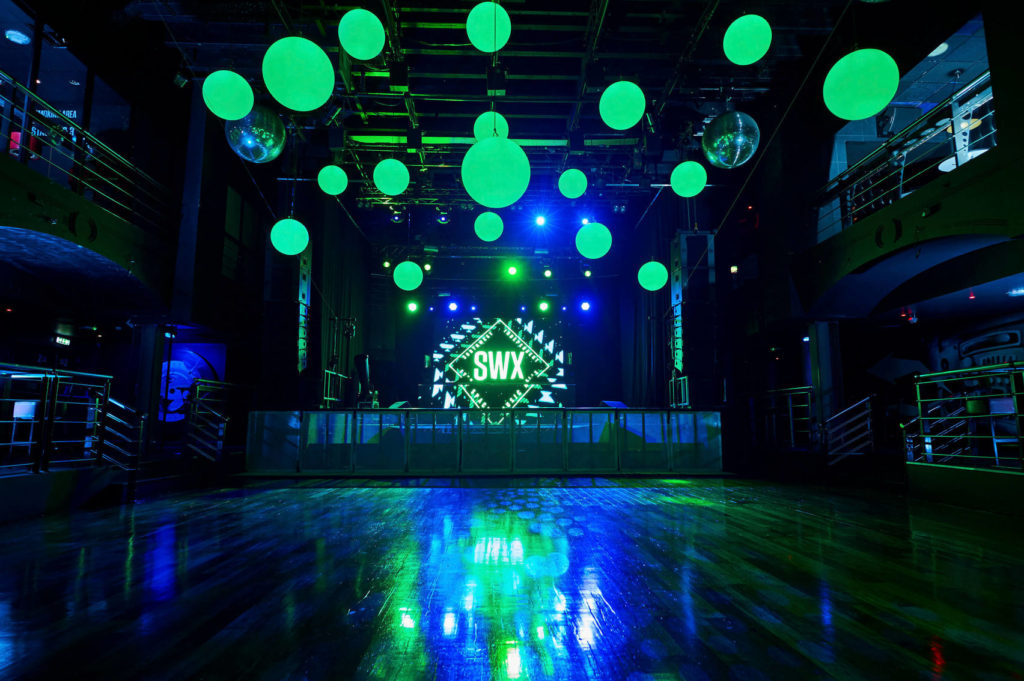 Dance floor with blue and green lighting and a stage area with SWX on a large screen