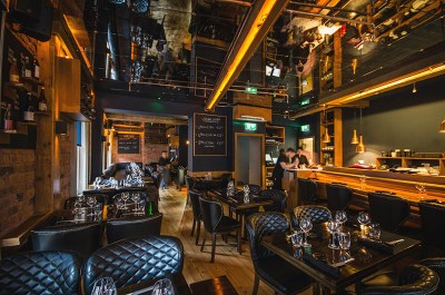 Dark restaurant with black leather seating and amber lights