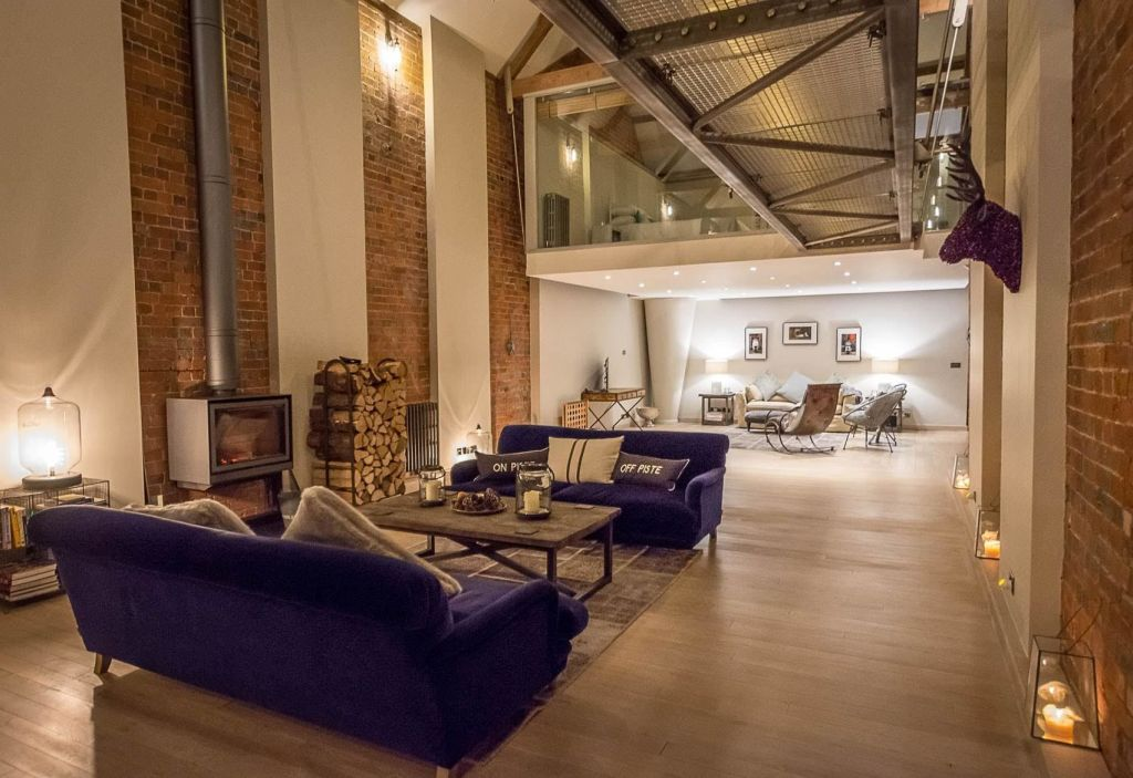 A modern and contemporary warehouse that has exposed brick and high ceilings. The space has a log fire, purple chairs and modern floor.