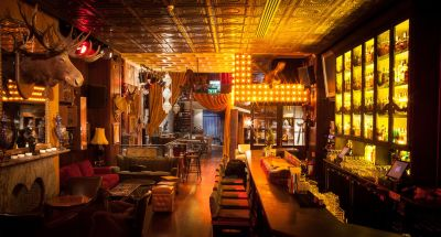 Dimly lit bar with amber lighting and leather seating