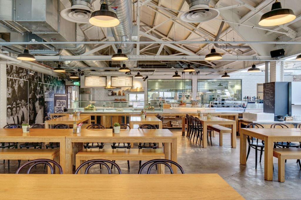 Industrial dining space with long wooden tables with hanging lights