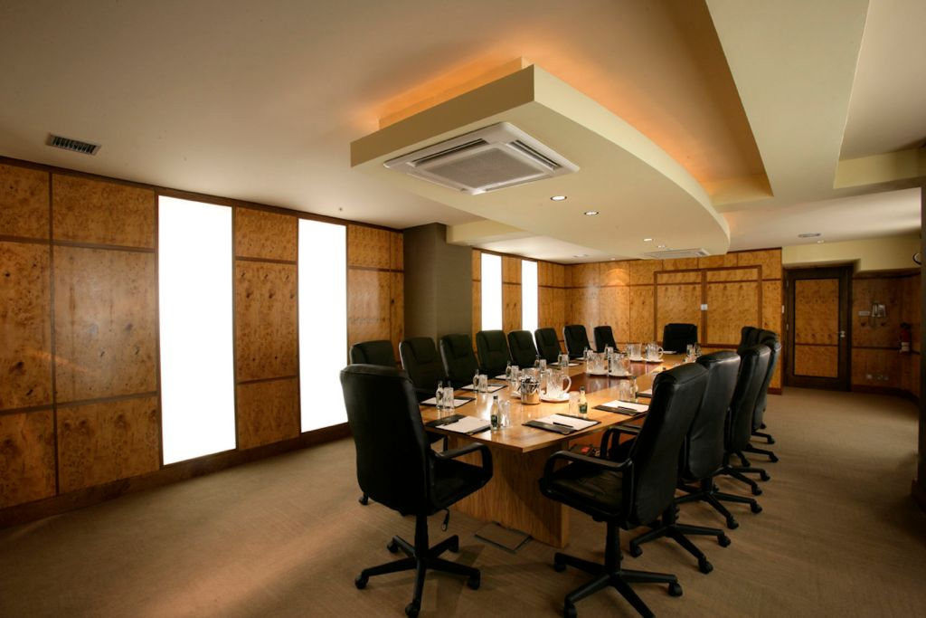 large board room with long wooden table, leather chairs and brown carpet