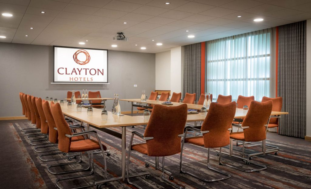 large meeting room with table set in u-shape with orange chairs facing a TV screen
