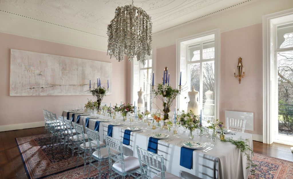 Private dining room with long table with chandelier, long windows and plants on the table