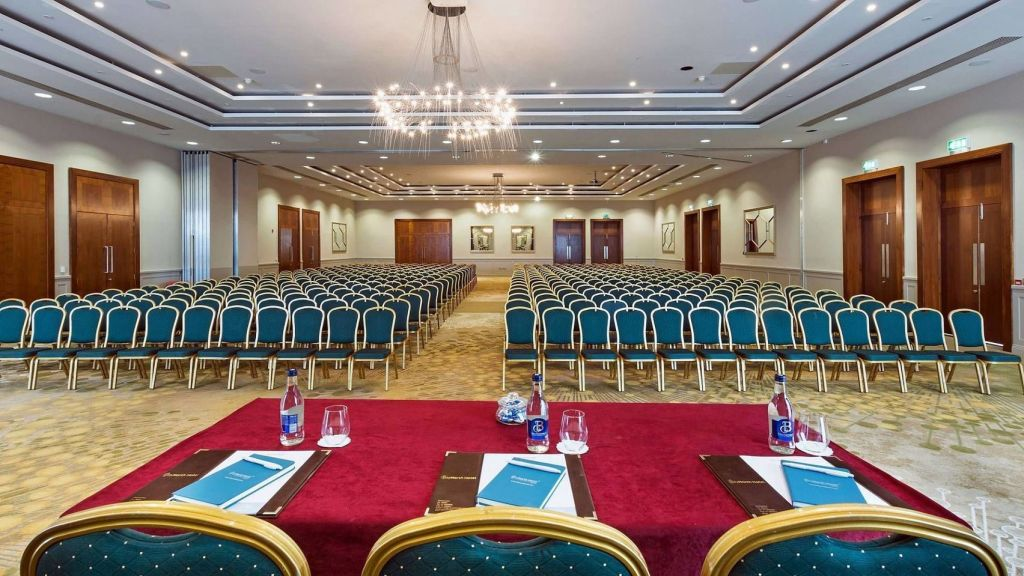large conference suite with rows of teal chairs facing a table with three chairs with a chandelier providing light