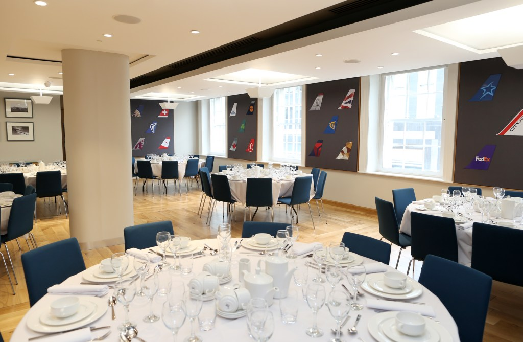 Function room with round tables with white tablecloths and tableware with windows letting in natural light