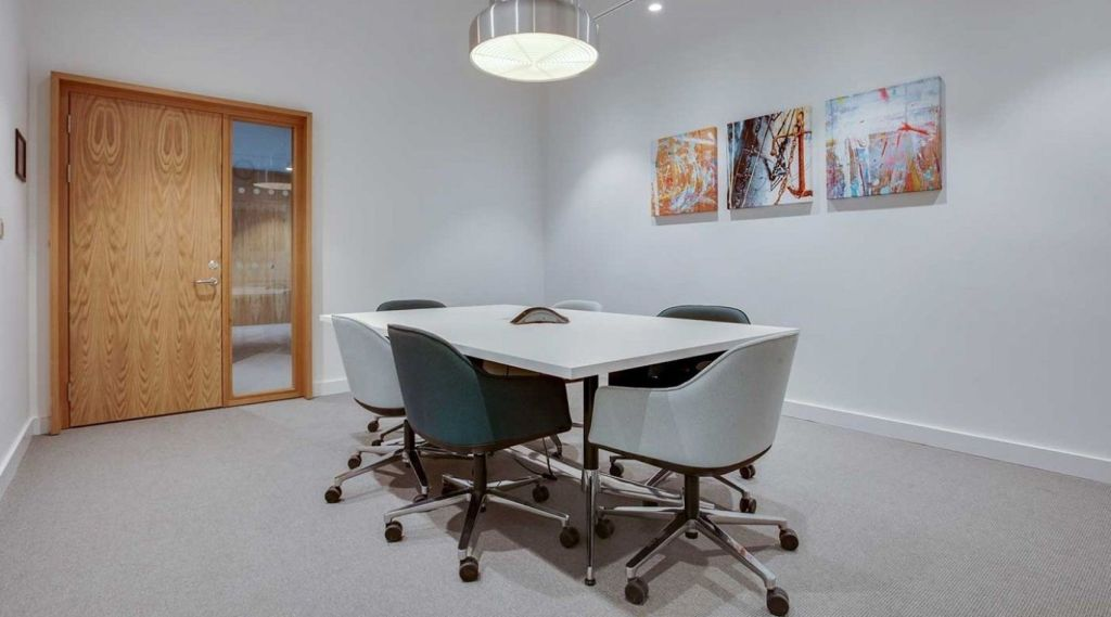 A white meeting room with a small white table in the middle surrounded by green chairs