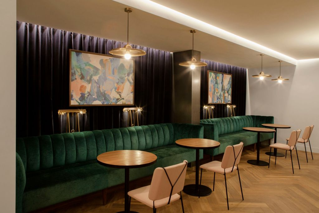 An unusual Space that has green velvet sofa seats across the back wall, small round wooden tables and light pink chairs