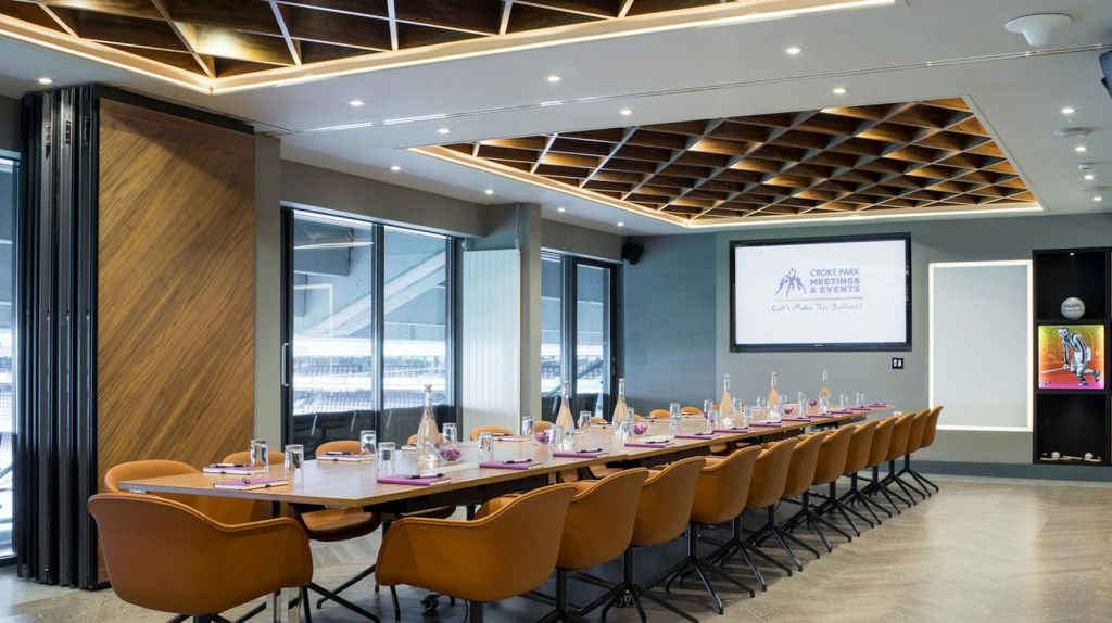A large meeting room which has one long table in the middle and a large glass wall which overlooks Croke Park