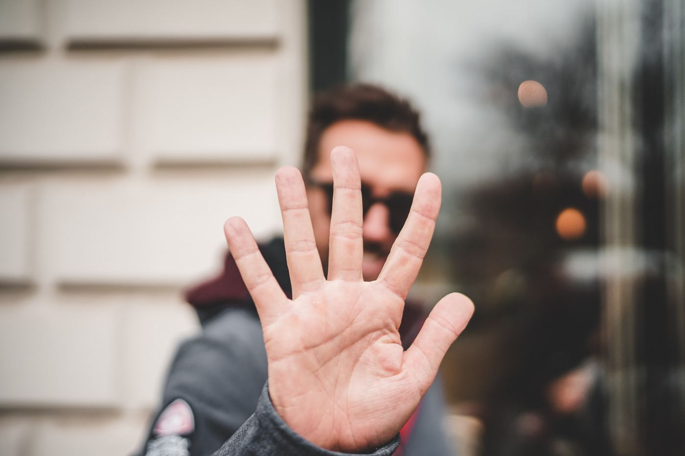 Man holding up 5 fingers to camera