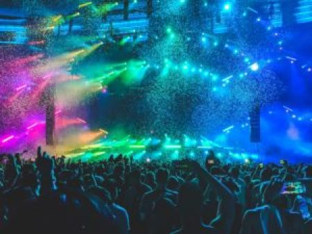 People facing a stage with multi colour light