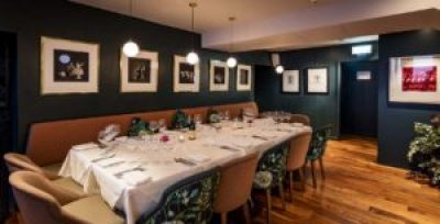 private dining room with wooden floors, art on the wall and a long table
