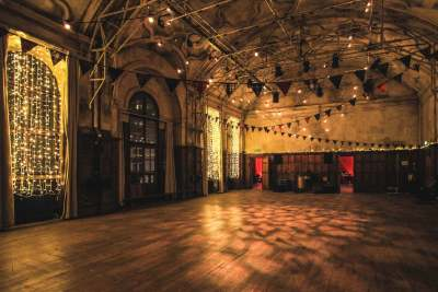 A small hall with curved ceiling, floor to ceiling arched windows and bunting