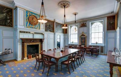 function room with wooden table, large windows, blue carpets and art on the walls