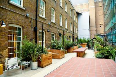 A rooftop terrance with wooden benches an lots of potted plants
