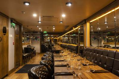 private dining room with long tables, mirrored walls and leather seating