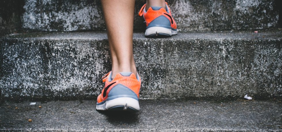 A runner in trainers climbing stone steps
