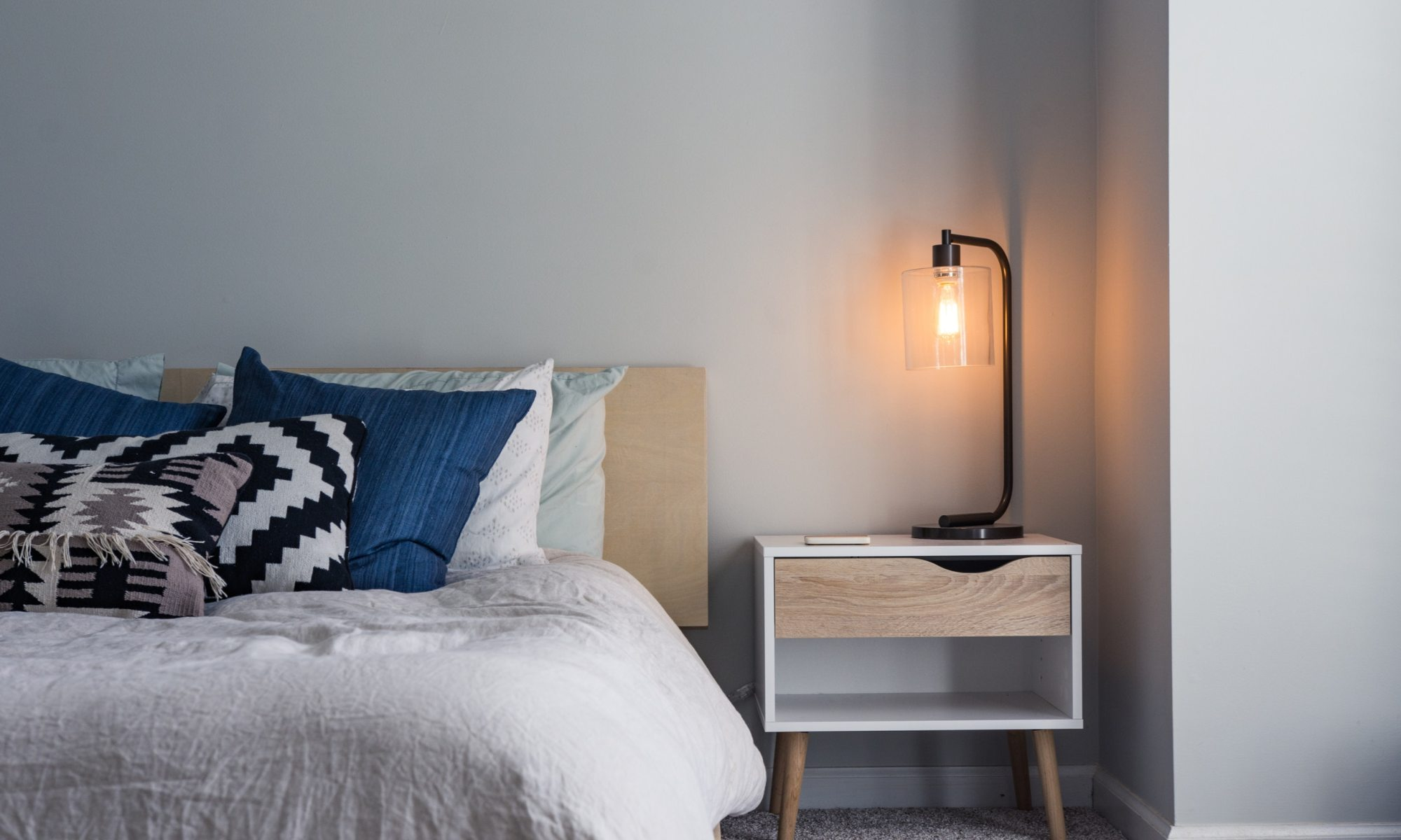 Bedroom with bed and mobile phone on nightstand