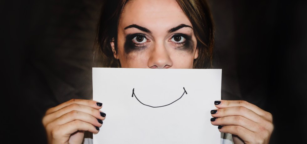 Unhappy woman who has been crying holding up a drawing of a smiley face over her mouth