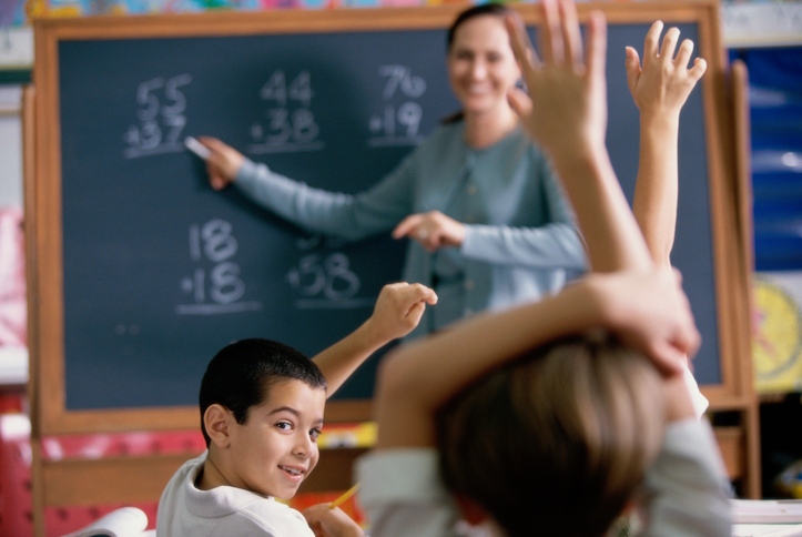 Female teacher pointing to a chalkboard in a classroom with her students raising their hands