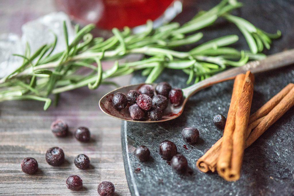Getränke zu Weihnachten: gefrorene Blaubeeren, Zimtstangen, Rosmarin
