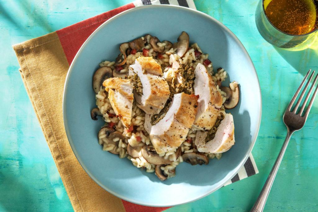 Mit Oliven gefüllte Hähnchenbrust auf einem Risotto mit Bacon und braunen Champignons