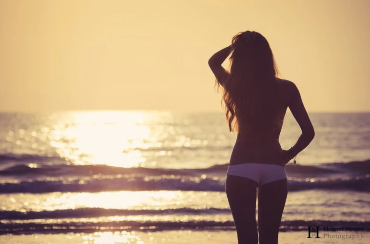 Girl looking into the sunrise at the beach