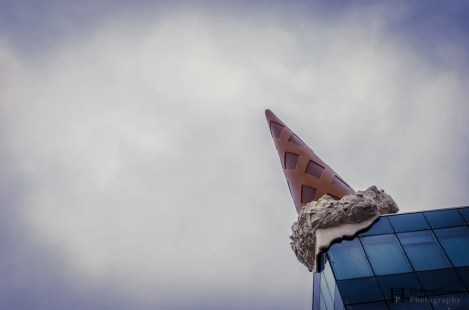 A building with a dropped ice cream cone on the roof