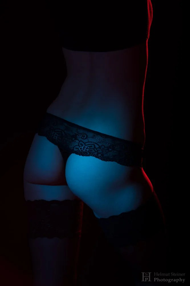 Female buttocks illuminated by red and blue light, lingerie