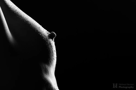black and white image of a breast with waterdroplets