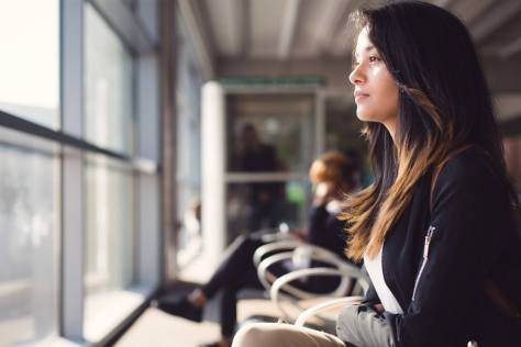 woman looking out window in airport