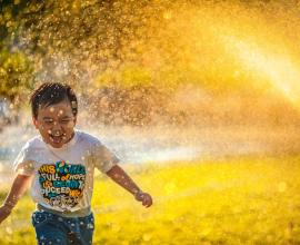 little boy playing and laughing, in splash of water, sunset