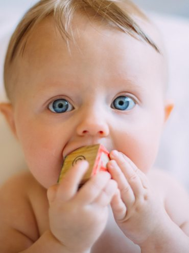 cute baby with blue eyes chewing a cube