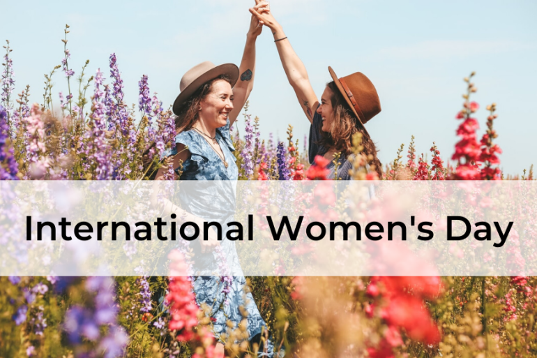 International Women's Day, two women in flower field holding hands and smiling