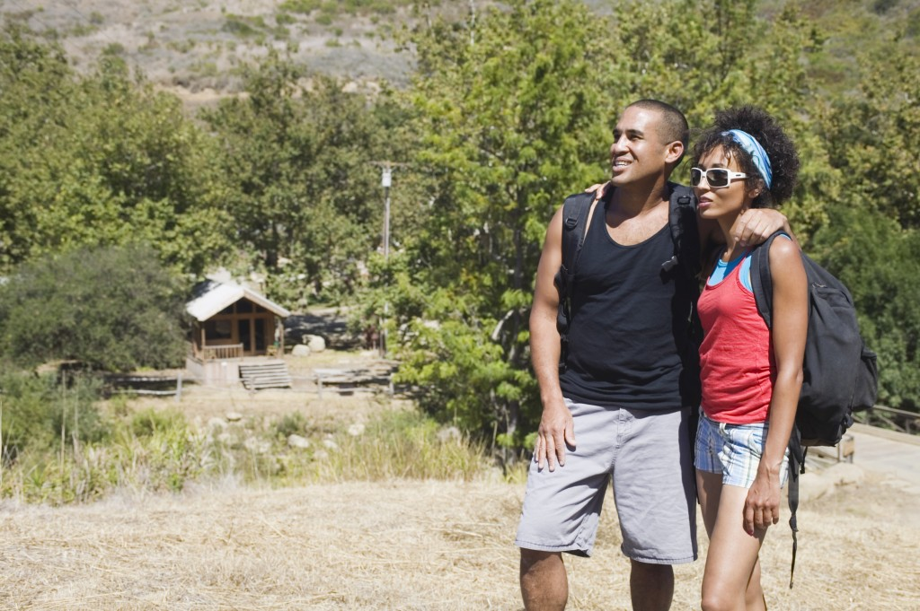 Couple with backpacks hugging outdoors