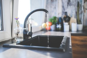 Kitchen sink dribbling water in a sleek kitchen.