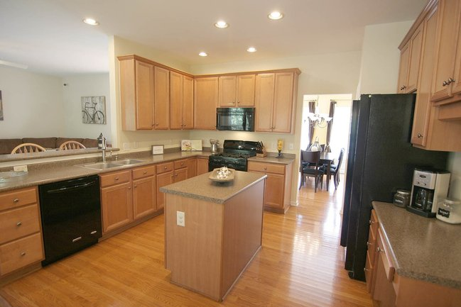 Spacious kitchen interior with wood paneling and an island.