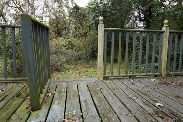 old backyard deck with leaning railing