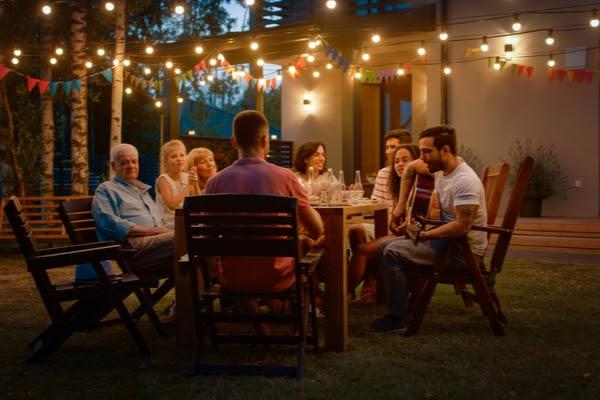 family enjoying backyard around table with lighting